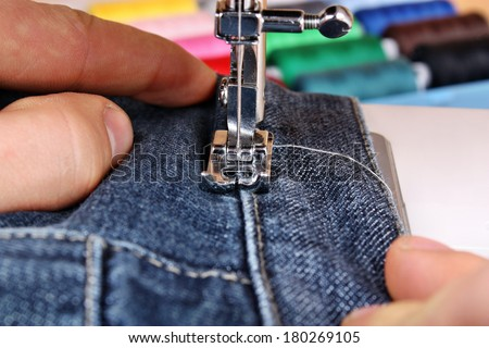 Sewing machine and item of clothing trousers jeans material - stock photo