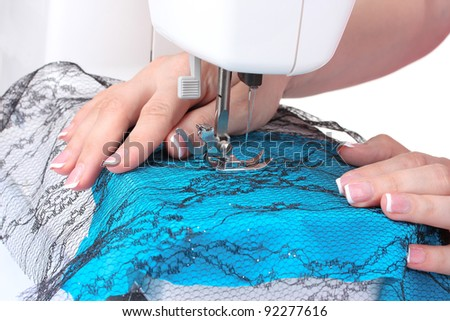 sewing machine, blue fabric and women's hands - stock photo