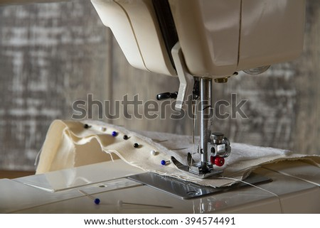 Sewing machine foot with fabric and pins in front of the wood wall