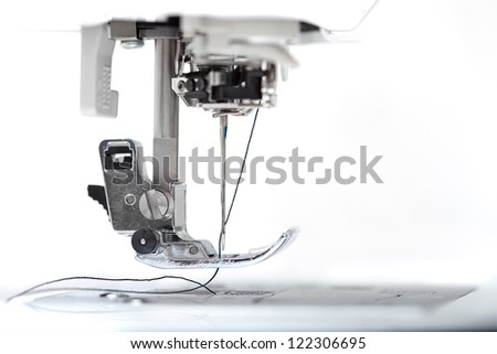 Sewing machine part with needle closeup on white background - stock photo
