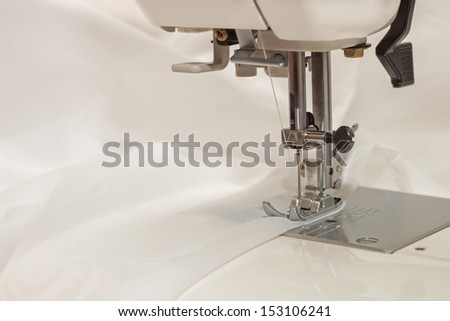 sewing machine sews a thin transparent veil of white cloth