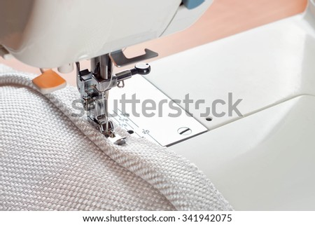 sewing machine. the process of sewing a decorative edging of white cloth. - stock photo