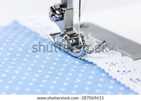 Sewing machine with blue cloth and white lace - stock photo
