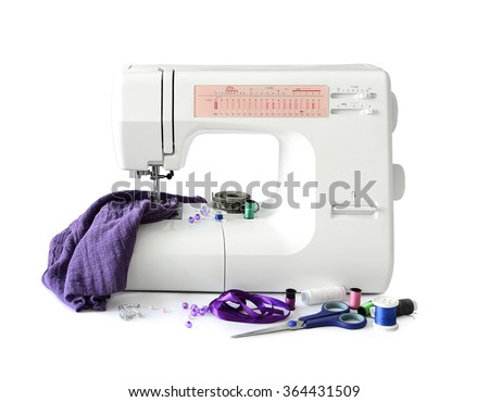 sewing machine with fabric and threads and scissors isolated on white background