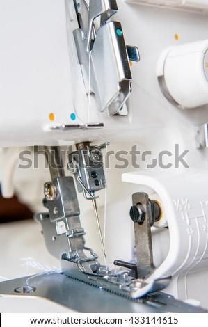 Sewing machine with fabric industrial overlock machine - stock photo