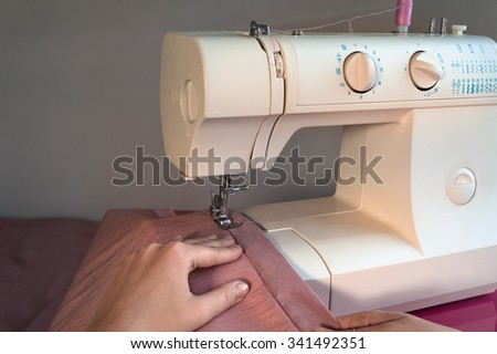 Sewing machine with women's hands - stock photo