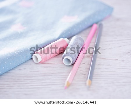 sewing materials, pencils, fabric on a blue and pink tone - stock photo