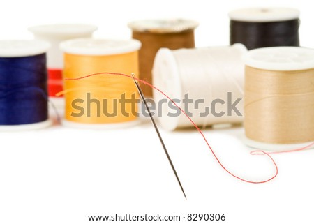 Sewing needle threaded with red, various colored spools in background - stock photo