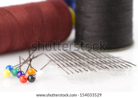 Sewing needles, pins and cotton thread - stock photo