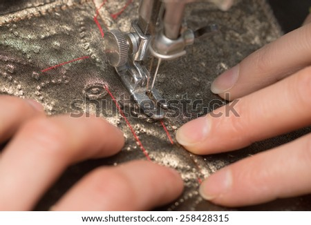 sewing on a sewing machine - stock photo