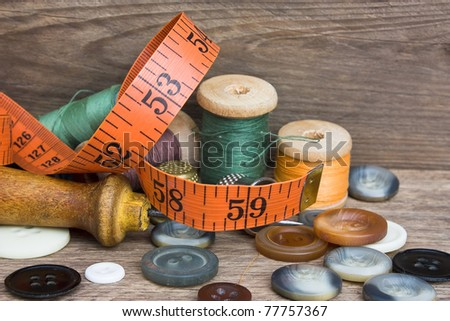 Sewing on the background of the old wooden walls - stock photo