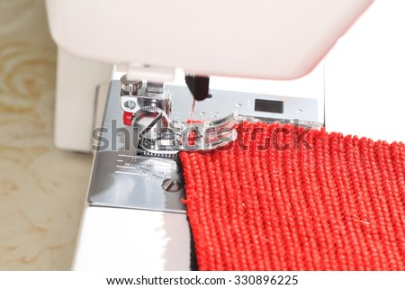 sewing on the sewing machine knitted fabric - stock photo