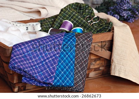 Sewing or quilting still life.  Basket of colorful cotton fabric and sewing notions.  Folded quilt and lavender in soft focus in the background. - stock photo