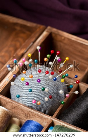 Sewing pins and pin cushion in wooden box - stock photo