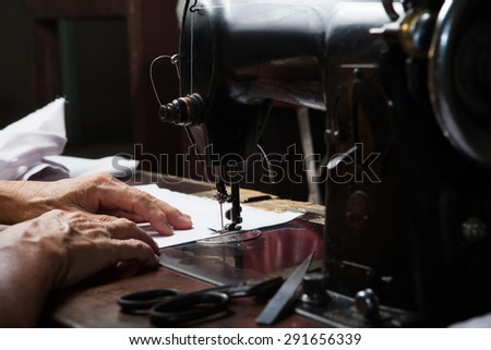 Sewing Process, Antique Sewing Machine with sewer, Lowkey lighting, Focus at needle - stock photo