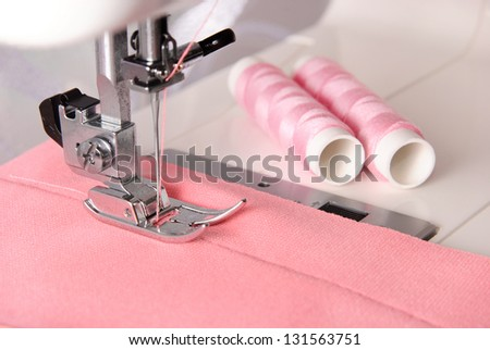 sewing process of rosy cloth on the machine and two bobbins background - stock photo