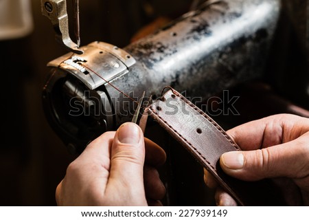 Sewing process of the leather belt. Man's hands behind sewing. - stock photo
