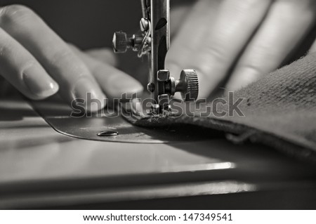 Sewing Process - Women's hands behind her sewing. Monochrome. - stock photo