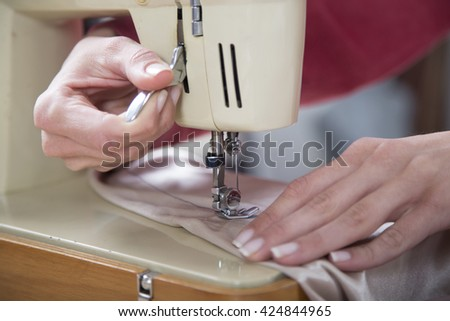Sewing Process - Women's hands behind her sewing,selective focus