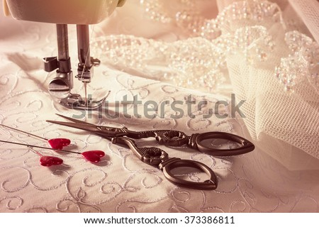 Sewing scissors with heart shaped pins on bridal dress fabric and lace - focus on scissors and pins - stock photo