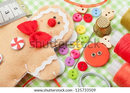 Sewing set and handmade gingerbread man from textile - stock photo