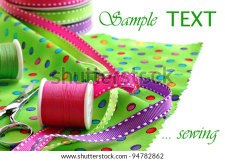 Sewing still life of brightly colored polka dot fabric with decorative ribbons. thread, and scissors on white background with copy space.  Macro with shallow dof. - stock photo
