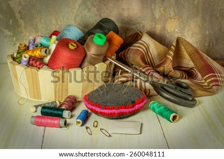 Sewing supplies: thread spools in a basket, fabric, needles, chalk, scissors. Toned photo. Selective focus - stock photo