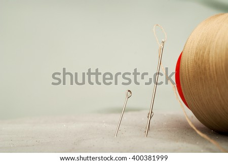 Sewing textile or cloth. Work table of a tailor. Detail of a needle with thread in the workroom reel of thread, and natural fabric. . Shallow depth of field. Focus on needle. Copy space. - stock photo