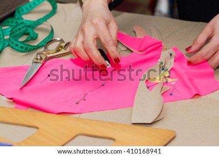 Sewing textile or cloth. Work table of a tailor. Textile tools. Scissors reel of thread,  measuring tapes and natural fabric. Copy space. - stock photo