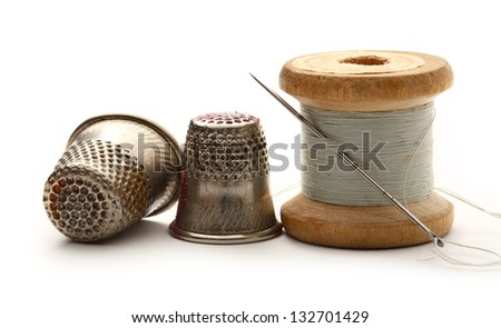 Sewing thimbles, bobbin and needle - stock photo
