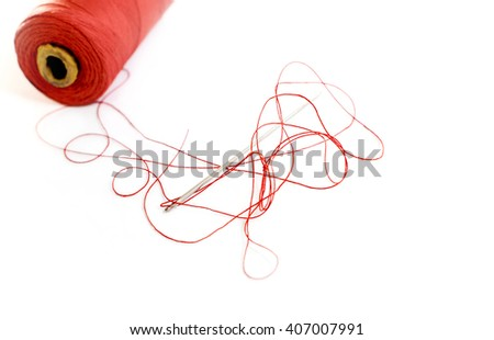 Sewing thread and needle on a white background closeup - stock photo
