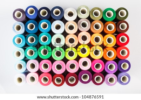 Sewing threads as a multicolored background closeup - stock photo