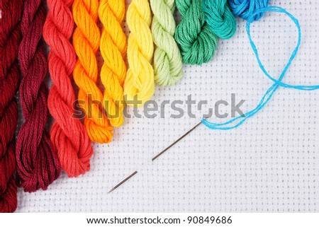 sewing threads for embroidery and  needle with a thread on white cotton - stock photo