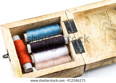 Sewing threads multicolored background closeup / Spools of thread peach color isolated on a white background / wooden casket case / colored thread on a wooden background - stock photo