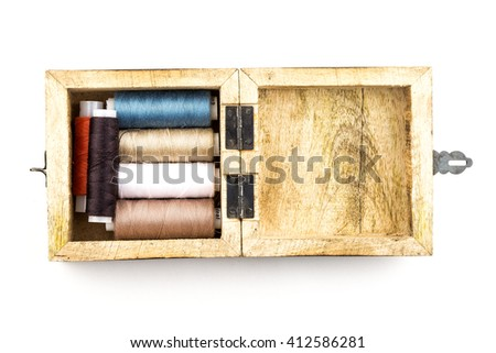 Sewing threads multicolored background closeup / Spools of thread peach color isolated on a white background / wooden casket case / colored thread on a wooden background