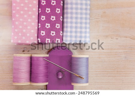Sewing threads, needle and fabrics on a wooden box - stock photo