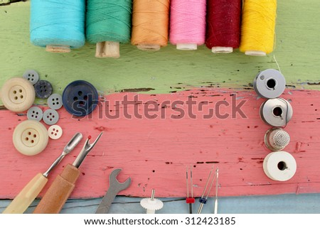 Sewing tools - bobbins with thread and needles on the old wooden background - stock photo