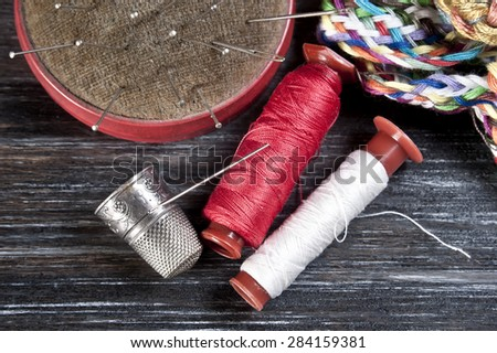 Sewing tools on wooden surface - stock photo