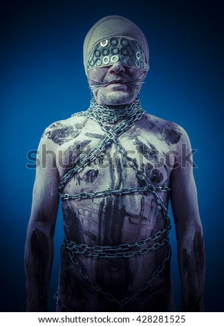 sex bdsm, man with chains by the body and wire glasses, skin painted black paint and white