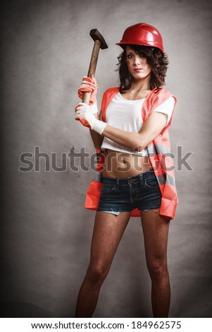 Sex equality and feminism. Sexy girl in workwear safety helmet and orange vest holding hammer tool on gray. Young attractive woman working as construction worker. Studio shot. - stock photo
