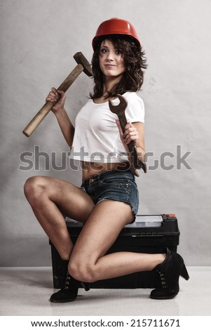 Sex equality and feminism. Sexy girl sitting on toolbox holding wrench spanner and hammer tools. Woman working as mechanic. - stock photo