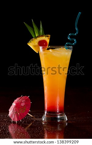 sex on the beach cocktail served on a bar garnished with a pineapple slice and a cherry