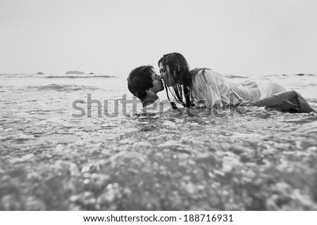 sex on the beach, young couple kissing in the water, black and white - stock photo