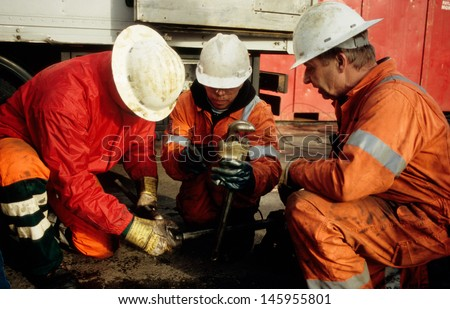 SEXBIERUM, THE NETHERLANDS-CIRCA NOVEMBER 2008 : Rig-personnel in the salt-mining industry being occupied with wireline-tools in Sexbierum, the Netherlands on circa November 2008 - stock photo