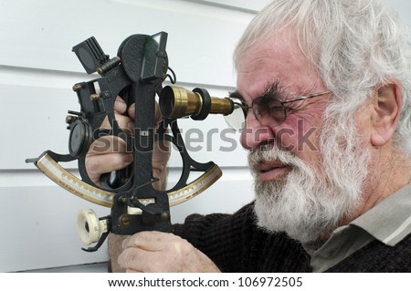 Sextant reflecting instrument.Sea Navigator man using a sextant. It's an old navigation instrument primary used to determine the angle between a celestial object and the horizon on a watercraft at sea - stock photo