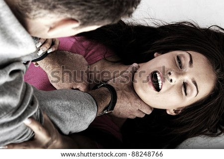 Sexual abuse concept. Brutal man reapeing young woman - stock photo