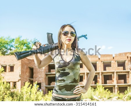 Sexual asian woman in the army. Sexy young adult woman spies in khaki uniform outfits hold in hand automatic machine or guns against red brick abandoned building. Kalashnikov assault rifle. Laser tag - stock photo