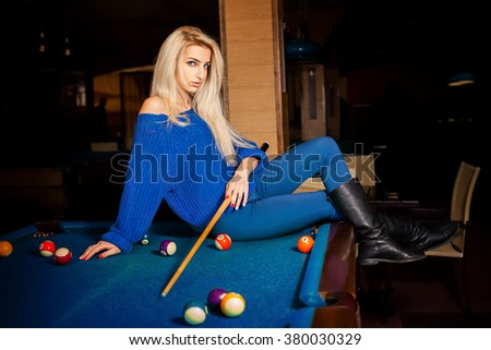 Sexual blonde lady posing on billiard table with the cue. Billiard sport concept. Pool billiard game. American pool billiard. - stock photo