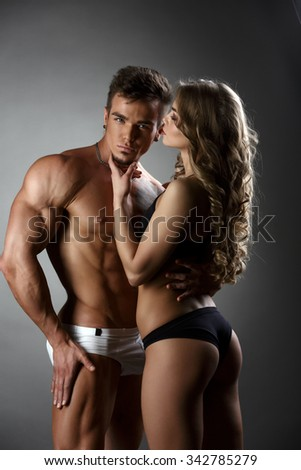 Sexual bodybuilder hugs girl possessively - stock photo