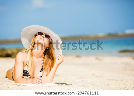 Sexual brunette girl take sunbath on the beach, happy female in  swimwear in sunglasses and white hat enjoying summer holidays leying on white sand. Holidays, vacation, lifestyle concept. Copyspace